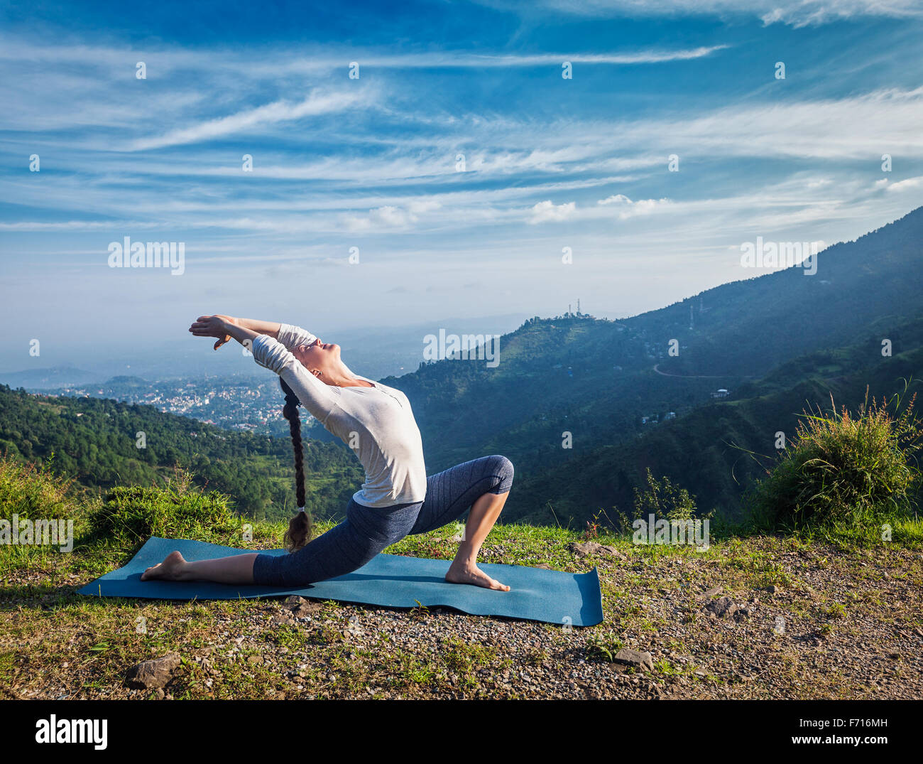 Woman practices yoga asana Anjaneyasana outdoors - Stock Image