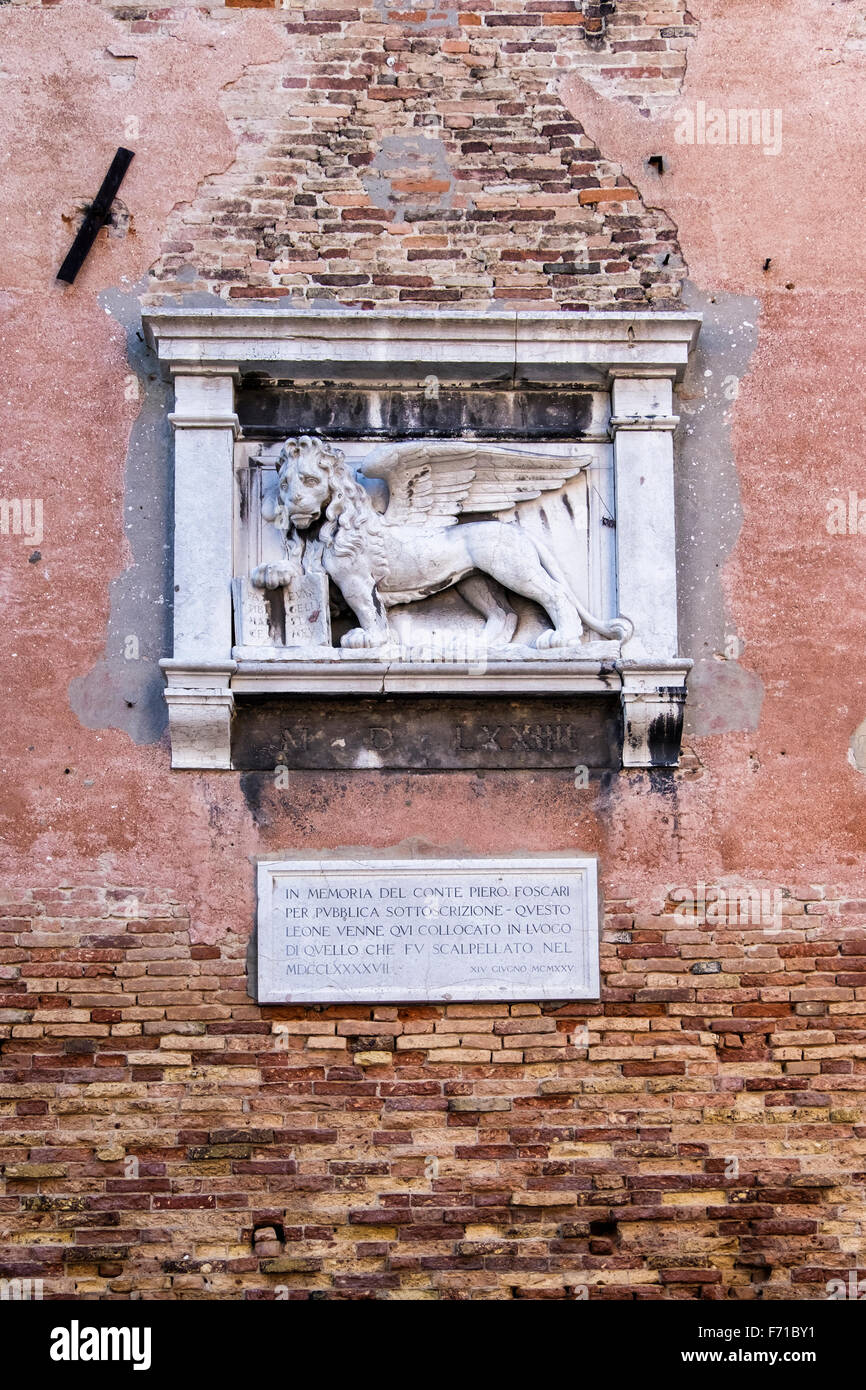 Venice, Italy. Sculptural detail, St Mark's lion memorial on a weathered, eroded urban brick wall - Stock Image