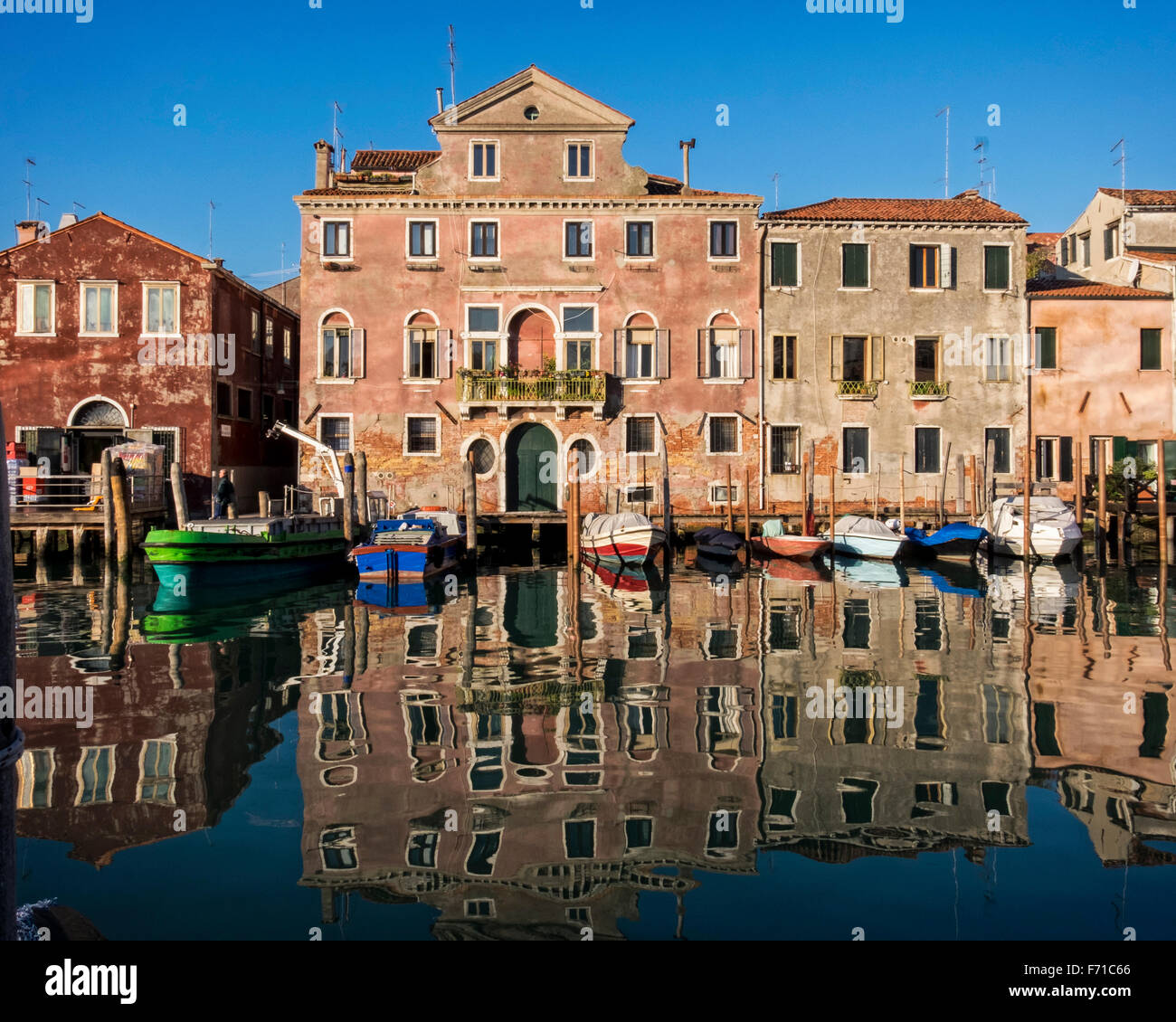 Venice, Castello, Sestiere, Italy - Harbour view - warehouse, Traditional houses, boats, reflections and warm colours - Stock Image