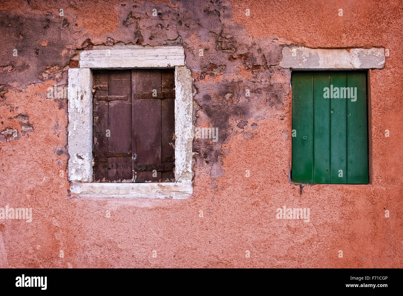 Venice Italy House exterior building detail, water damaged painted wall and shuttered windows - Stock Image