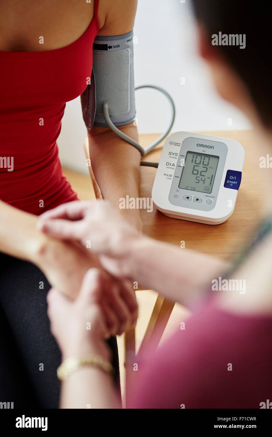 Doctor taking patients bloody pressure Stock Photo