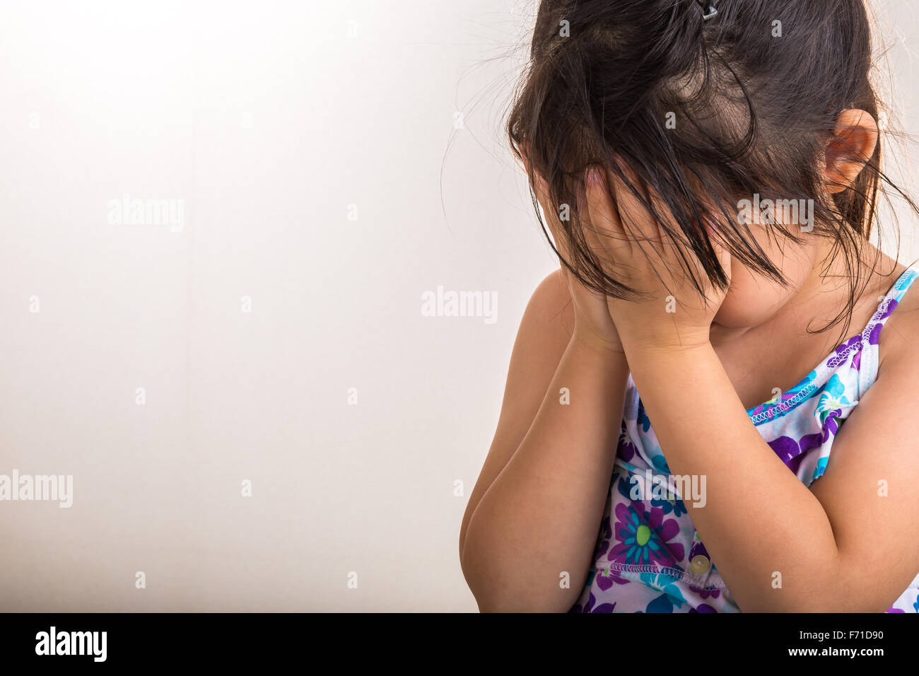 Little girl is playing hind-and-seek by covering her face with hands. - Stock Image