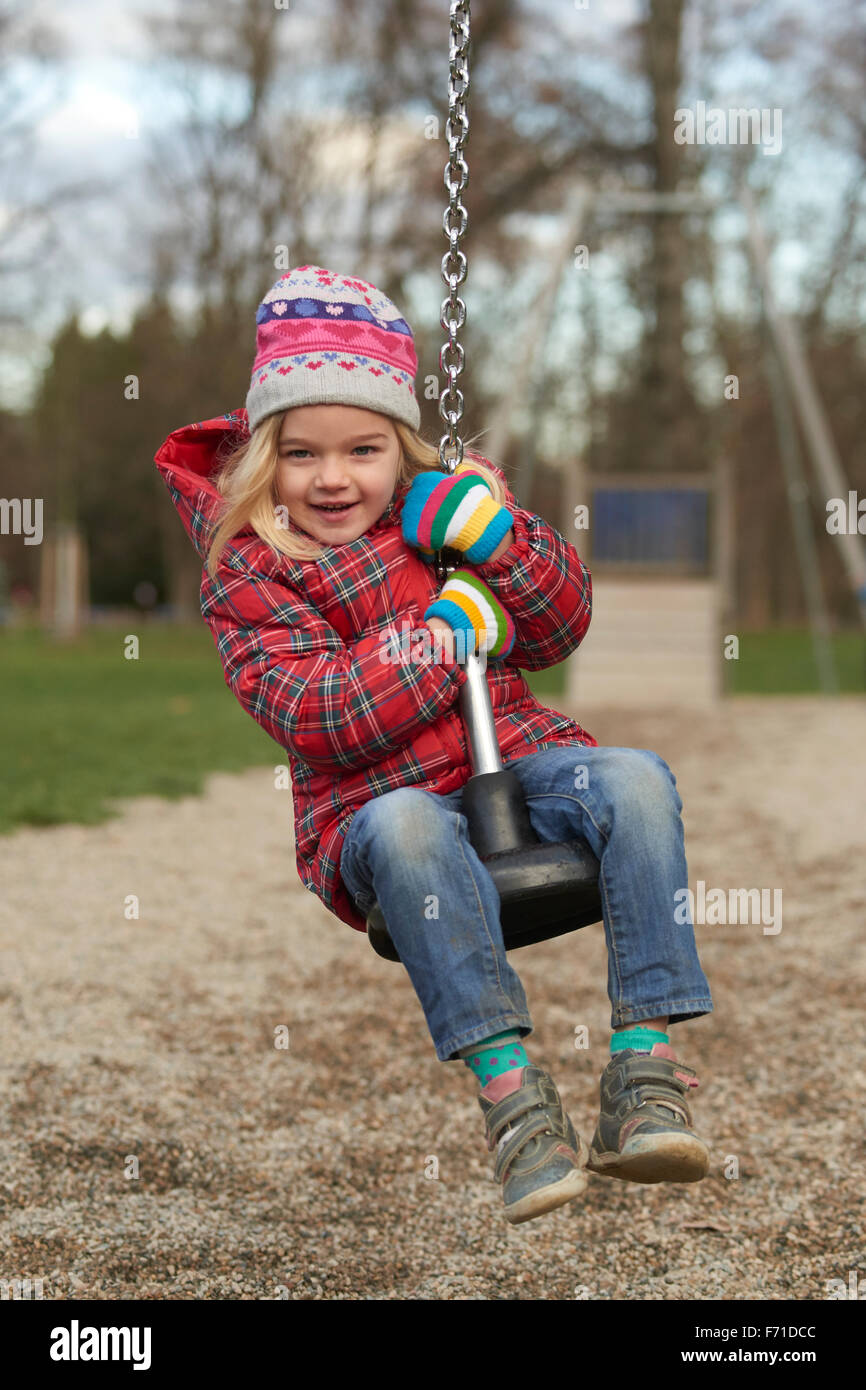 Child girl rids on Flying Fox play equipment in a children's playground. Seesaw, sliding, flying, rope slide - Stock Image