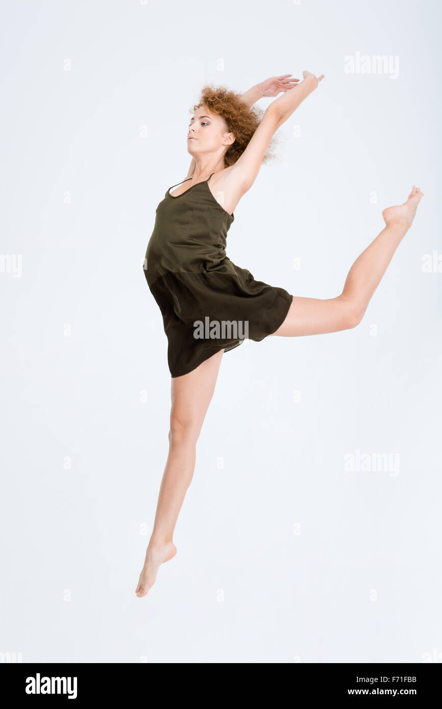 Full length portrait of a young woman dancing isolated on a white background - Stock Image