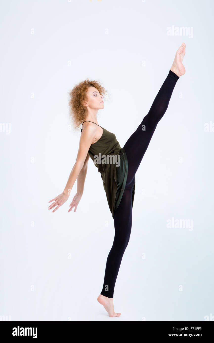 Full length portrait of a young flexible woman posing isolated on a white background - Stock Image