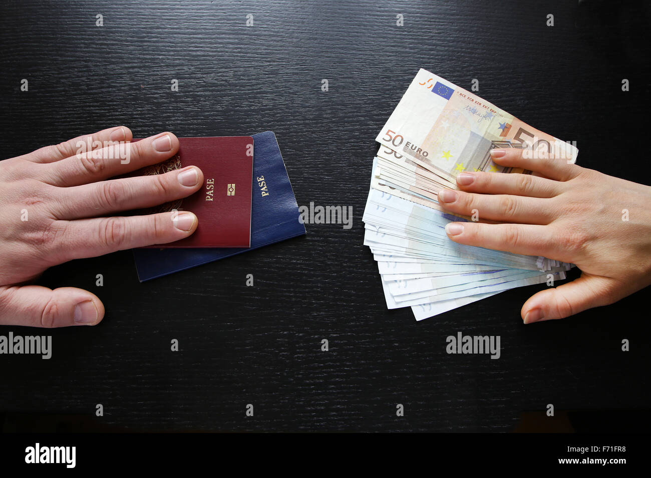 buying illegal foreign passport hands exchanging money and documents buyer seller - Stock Image