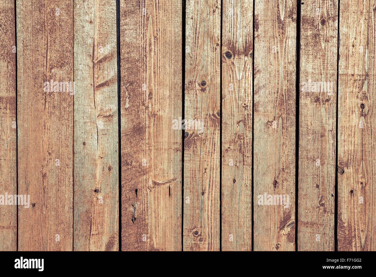 Old wood planks oriented vertically. Wood texture with weathered paint and cross process effect - Stock Image