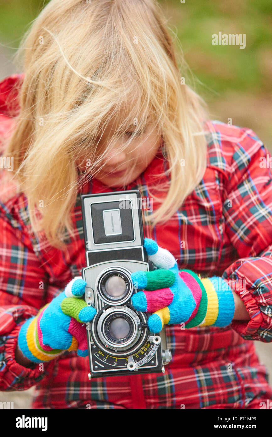 Close-up of girl photographing and looking at vintage analogue Twin-lens reflex camera, taking picture - Stock Image