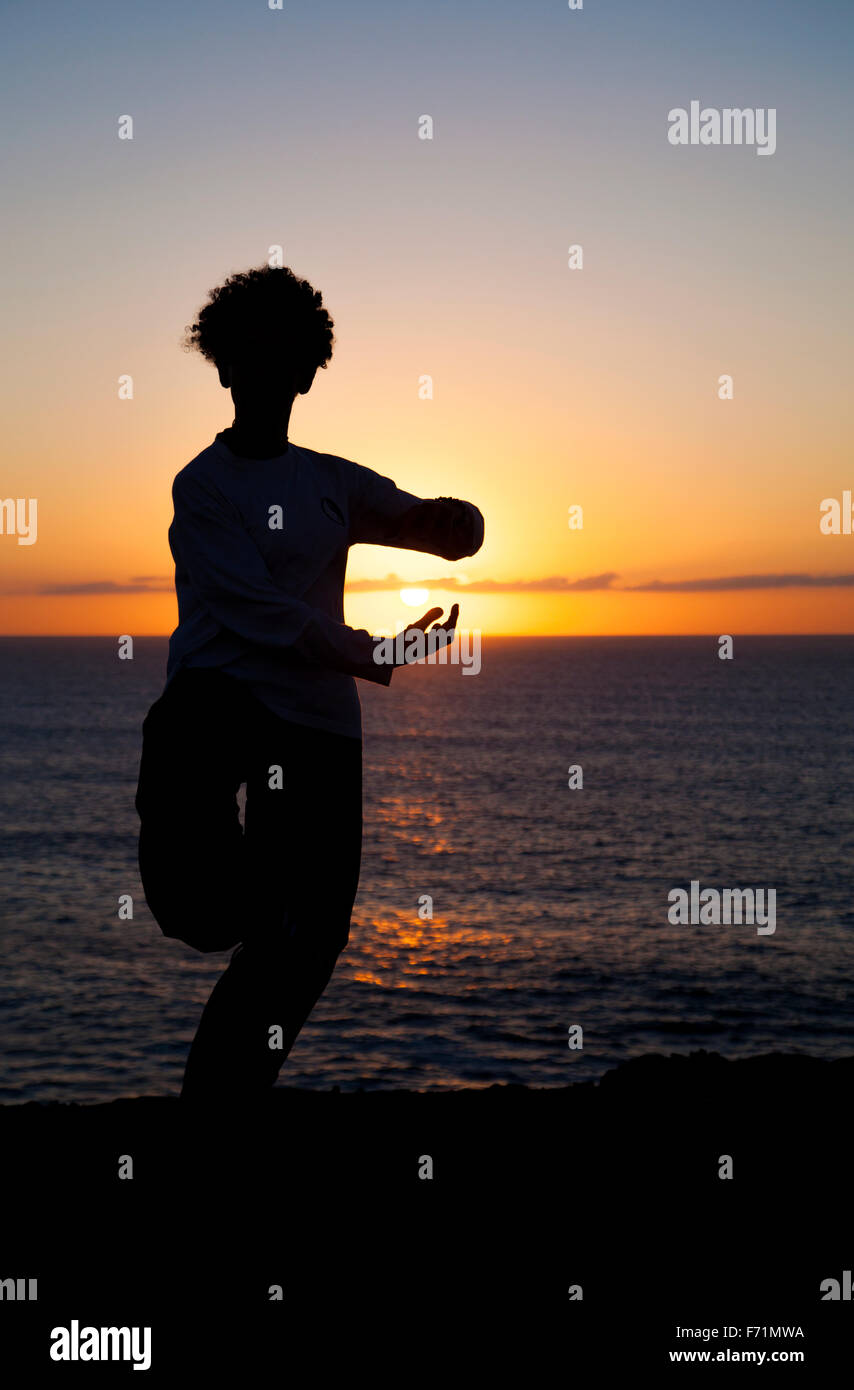 young woman performs tai chi moves silhouetted agains  sunset - Stock Image