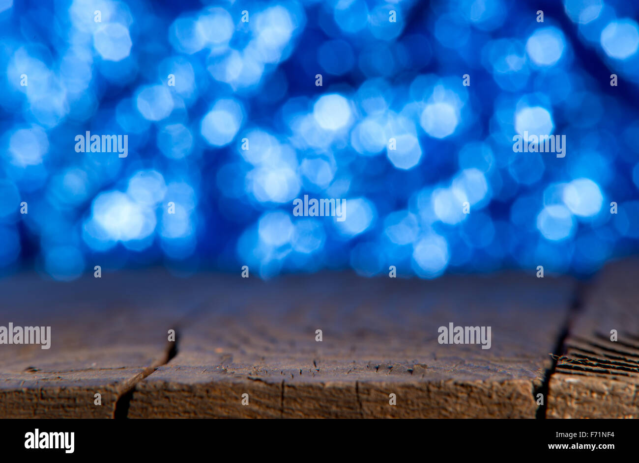 blue unfocused background with old wooden table - Stock Image