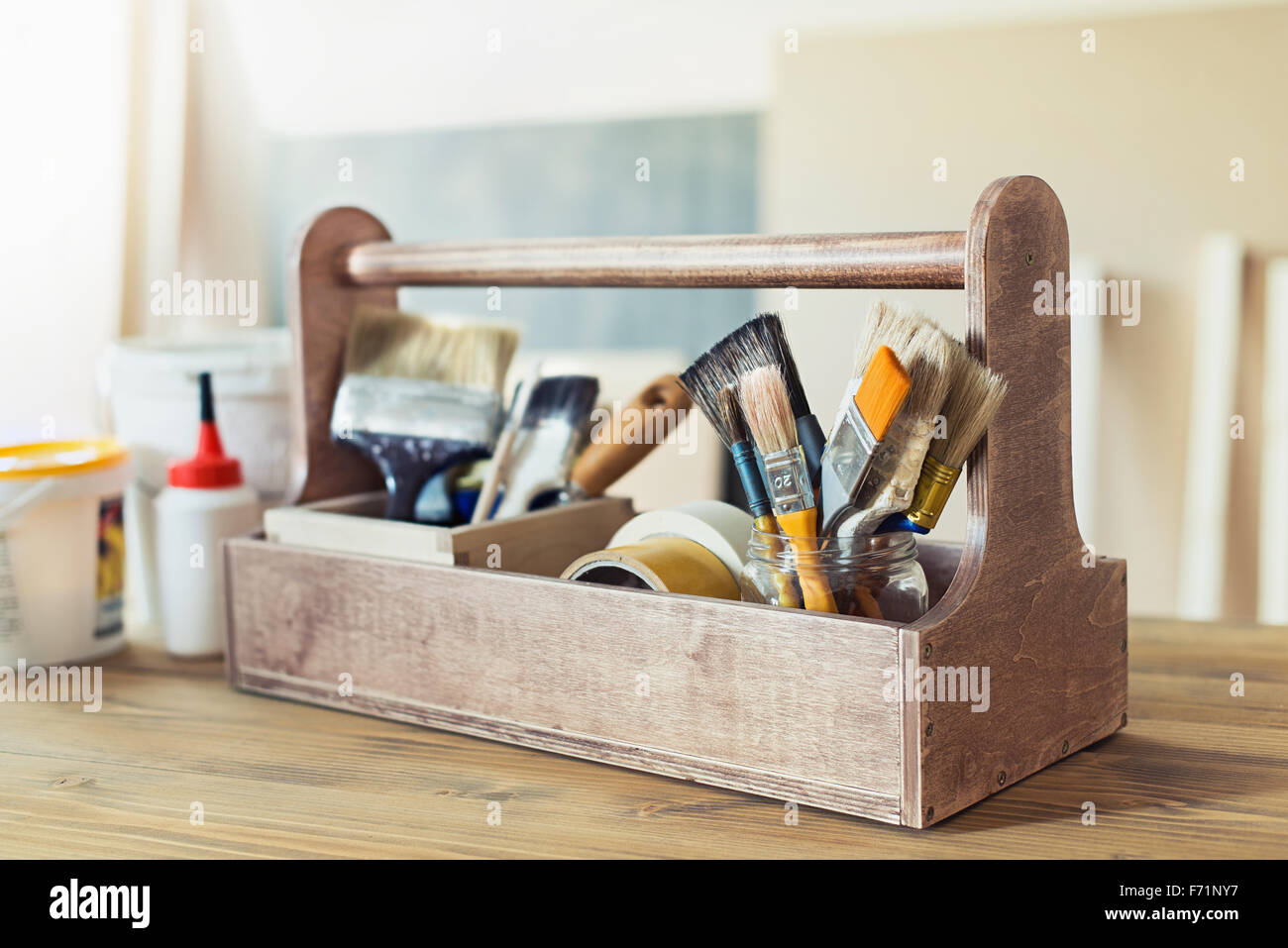 Paint brushes and crafting supplies in wooden toolbox - Stock Image