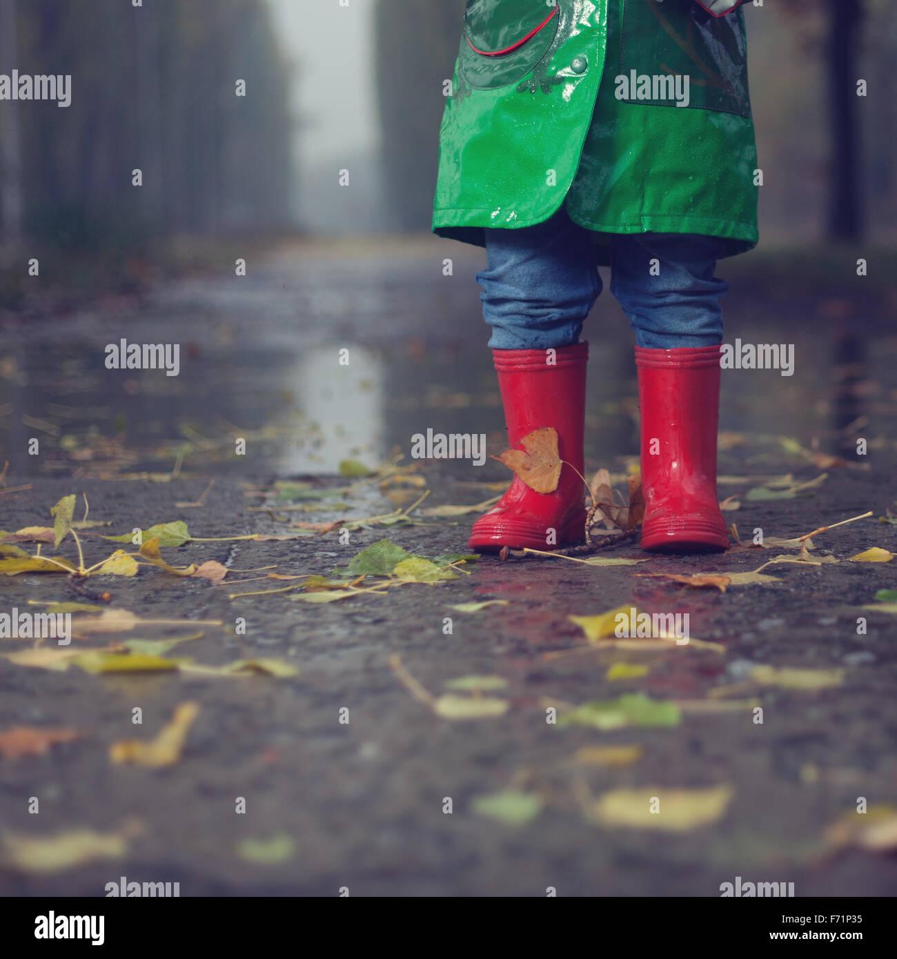Baby walking in autumn rainy park - Stock Image