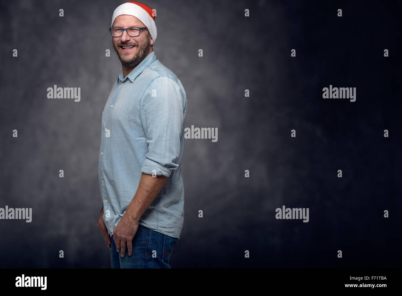 Three Quarter Shot of a Middle Aged Man, Wearing Santa Clause Hat, Smiling at the Camera, with Arms Crossing Over - Stock Image