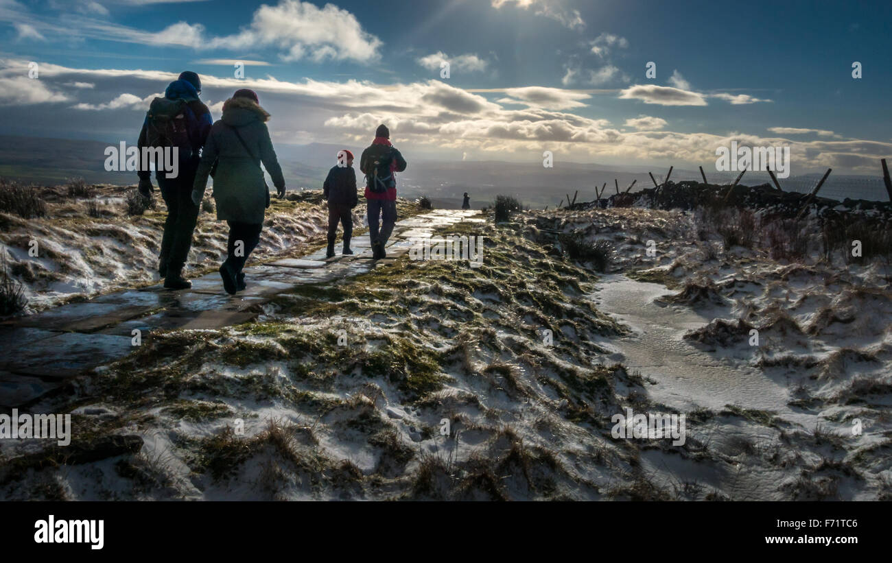 People walking off the summit of a snowy Pen-y-ghent mountain; one of the famous Yorkshire Three Peaks mountains - Stock Image
