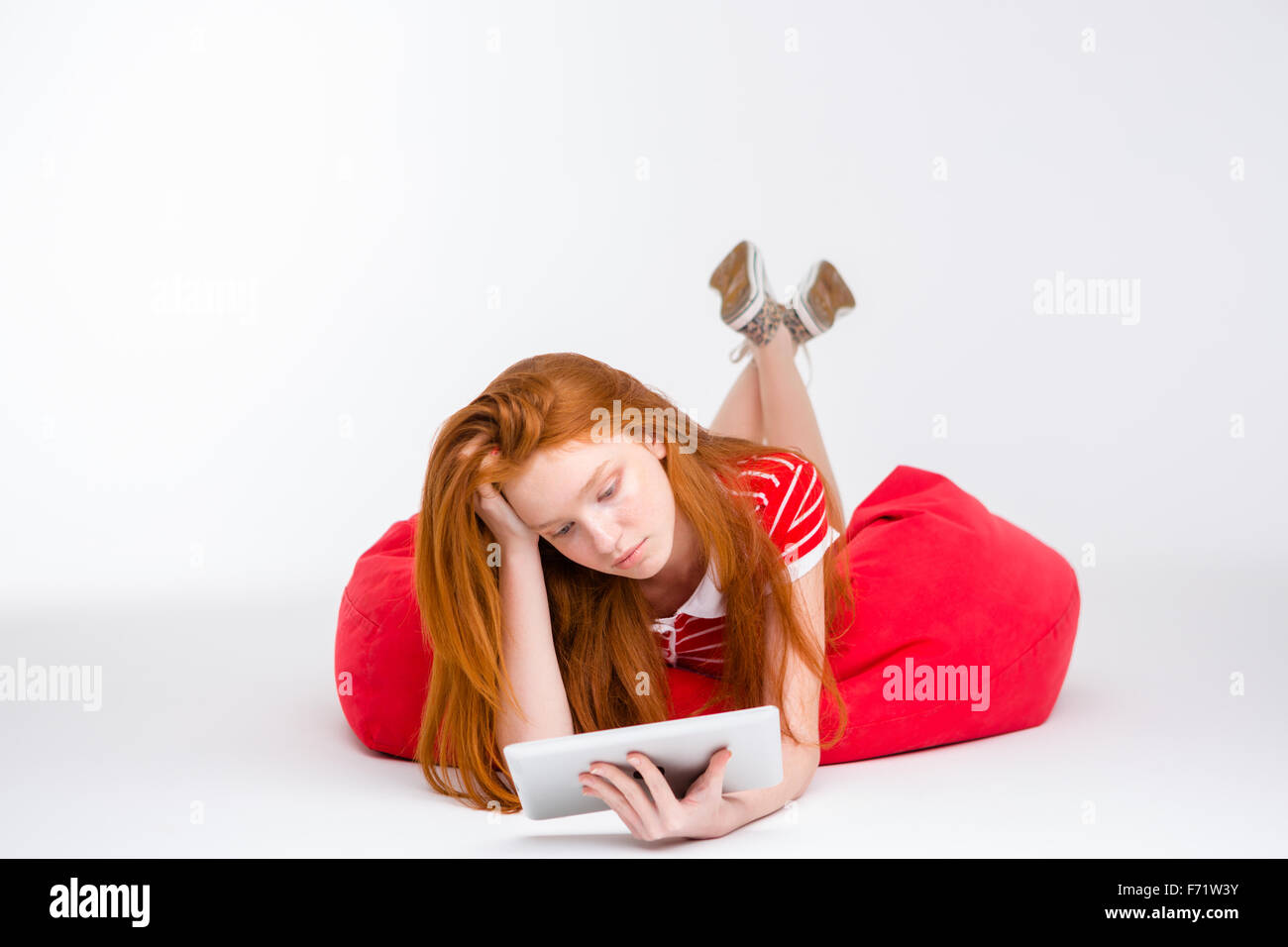 Tired exhausted girl with long red hair lying on red bean bag using tablet on white background - Stock Image