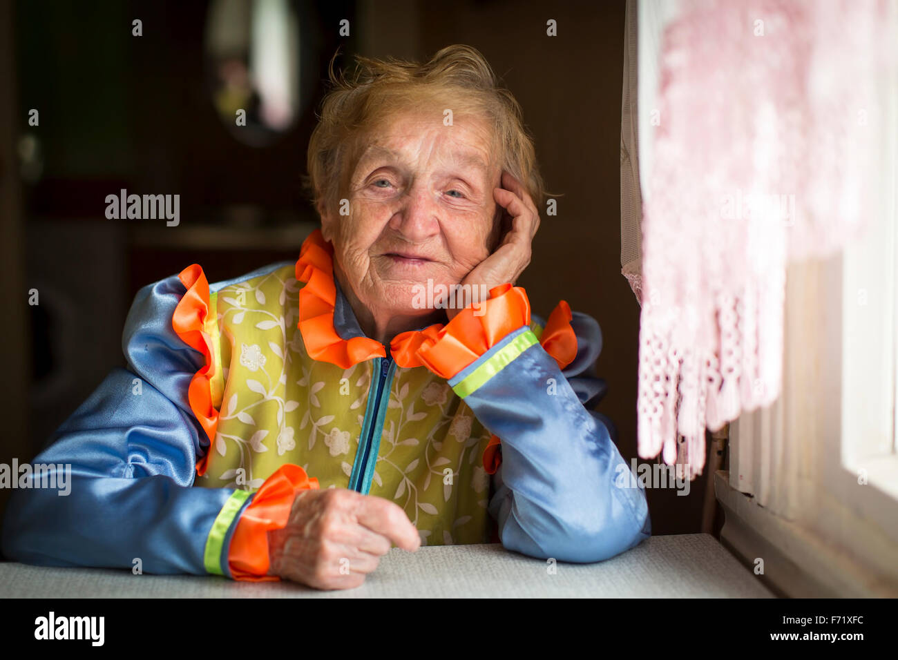 An elderly woman in Cossack clothes, a portrait by the window. - Stock Image