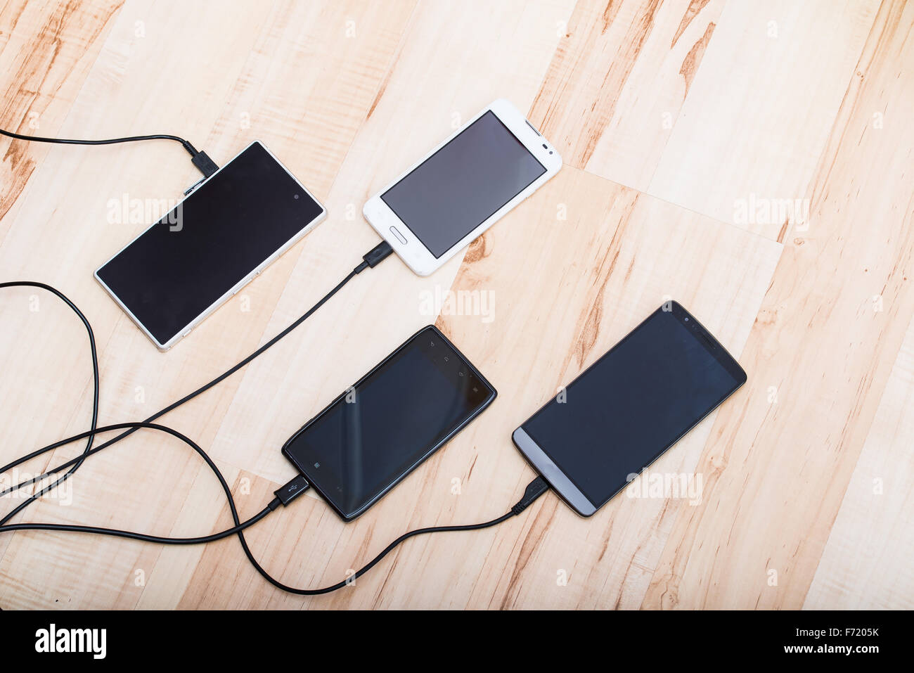 four smartphones connected to chargers - Stock Image