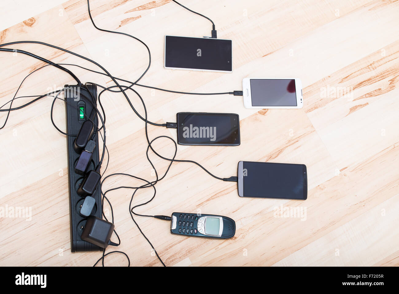 four smartphones and one classic phone connected to chargers - Stock Image