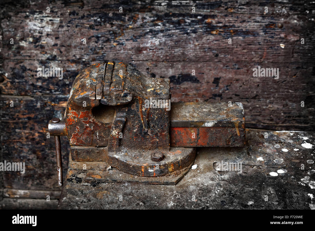 An old weathered and rusted vice on a workbench. - Stock Image