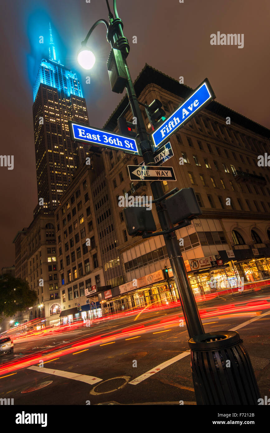 Night low angle view of the Empire State Building with teal color lights, Manhattan, New York, USA - Stock Image