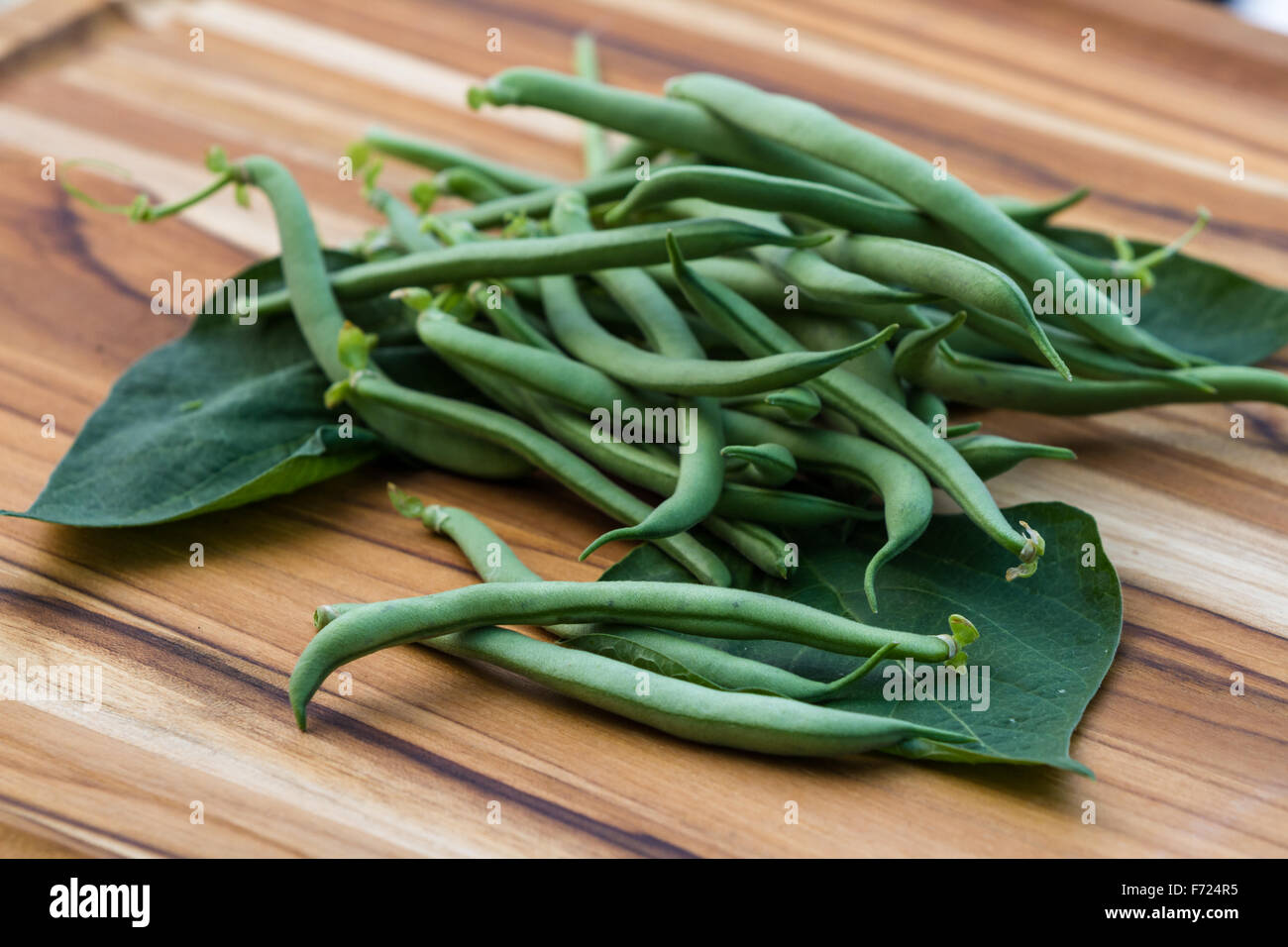 freshly picked organic green beans placed on a wooden table Stock Photo