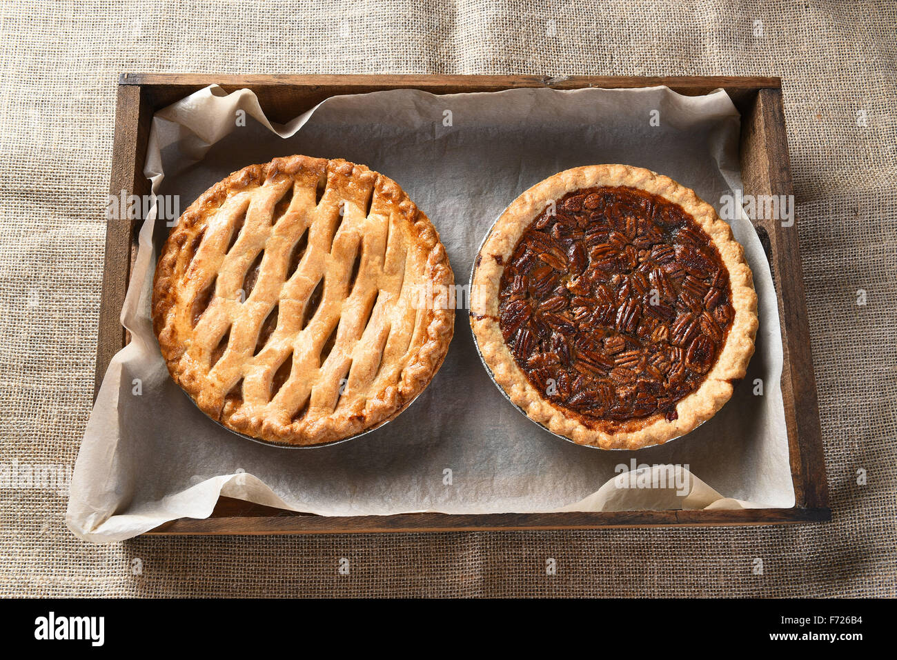 High angle view of an apple pie and pecan pie in a wood box lined with parchment paper. Horizontal format on a burlap - Stock Image
