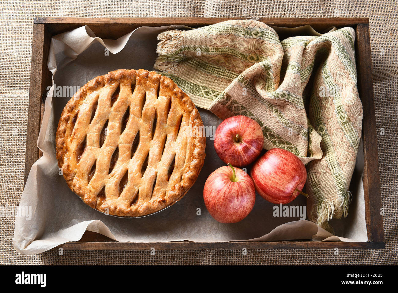 High angle view of a fresh baked apple pie and apples in a wood box on burlap surface. - Stock Image