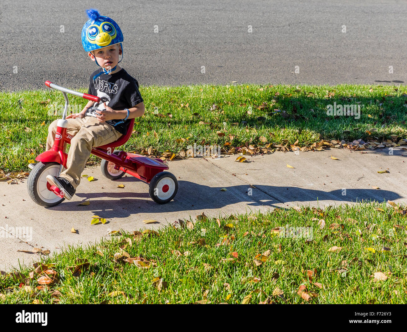 0c6518785f5 A toddler sits on his red tricycle on a sidewalk with his blue helmet on in  Chico, California.