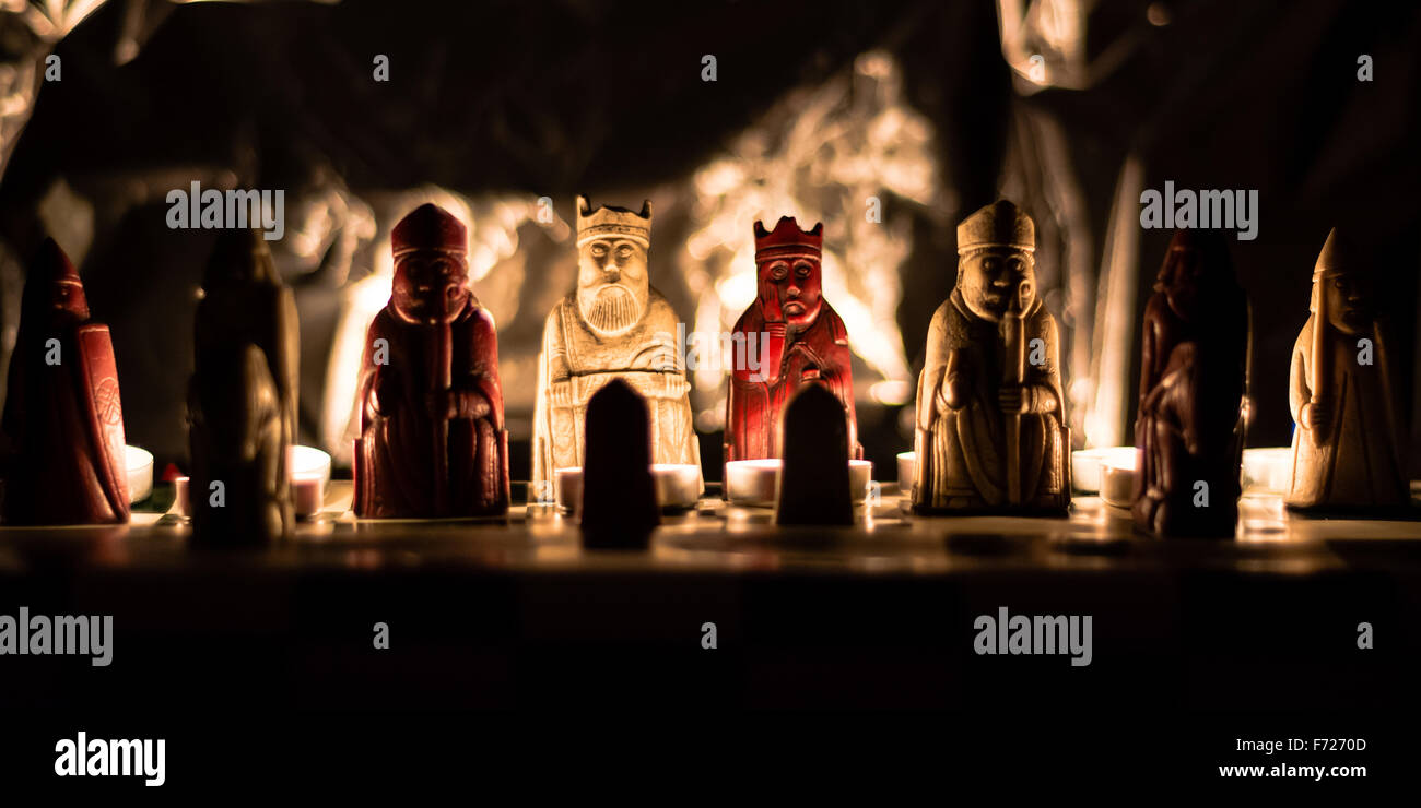 A replica set of the Lewis chess men, on board lit by candlelight - Stock Image