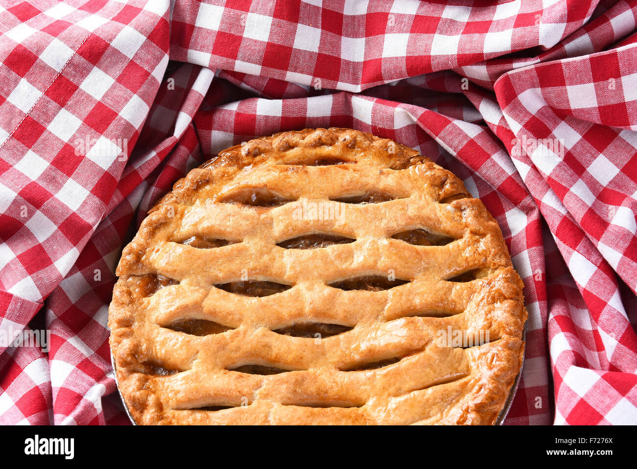 Closeup of a fresh baked Apple Pie surrounded by a red and white checked table cloth. - Stock Image