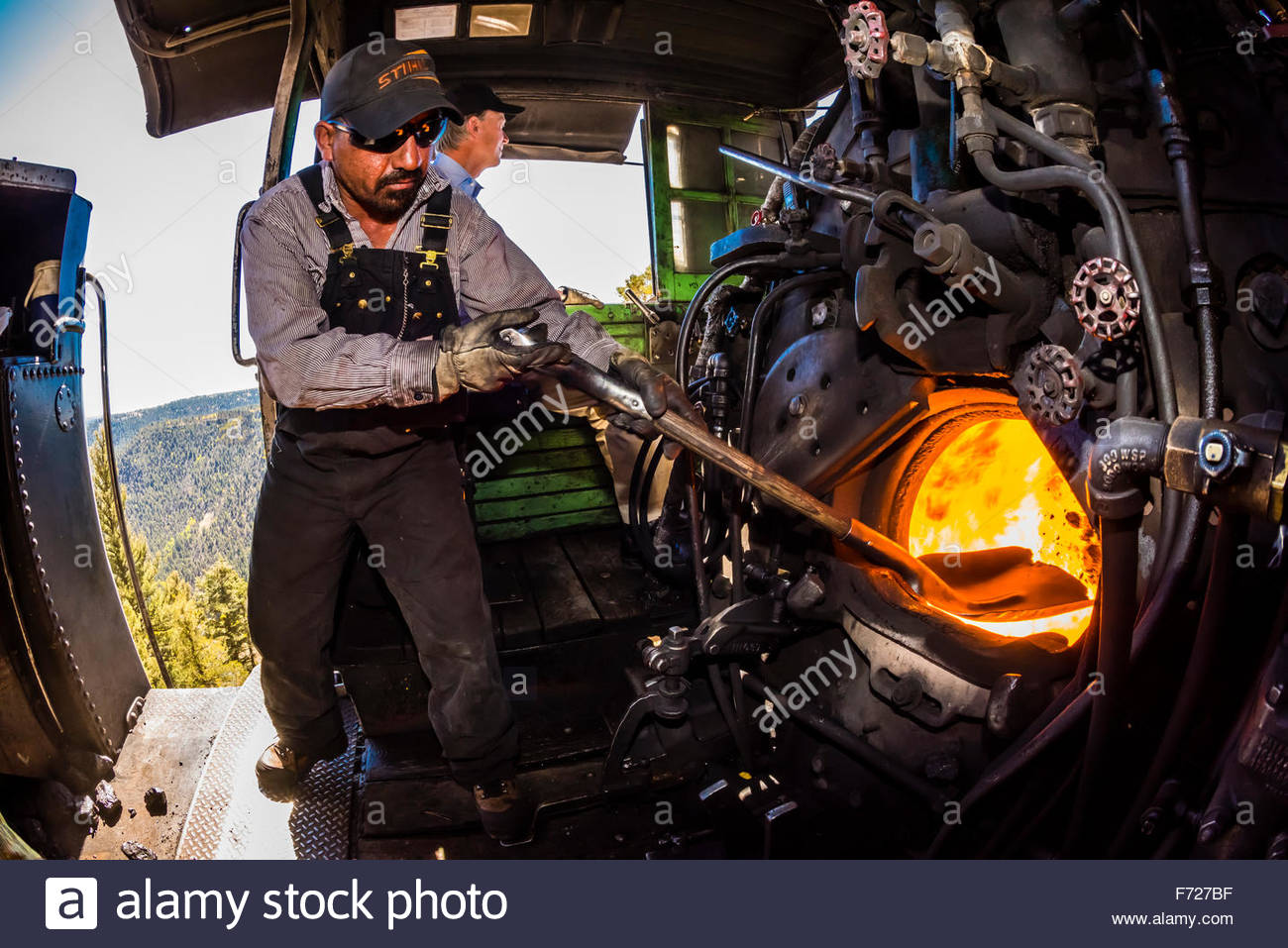 The fireman stokes the fire in the boiler of the steam engine (Colorado Governor John Hickenlooper sits behind), - Stock Image