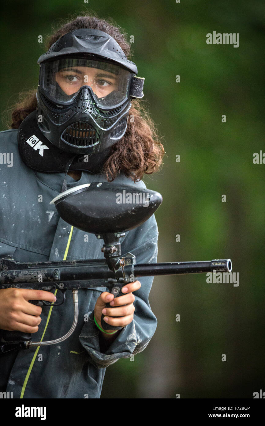 A paintball player girl at work. Jeune fille joueuse de paintball en action. Stock Photo