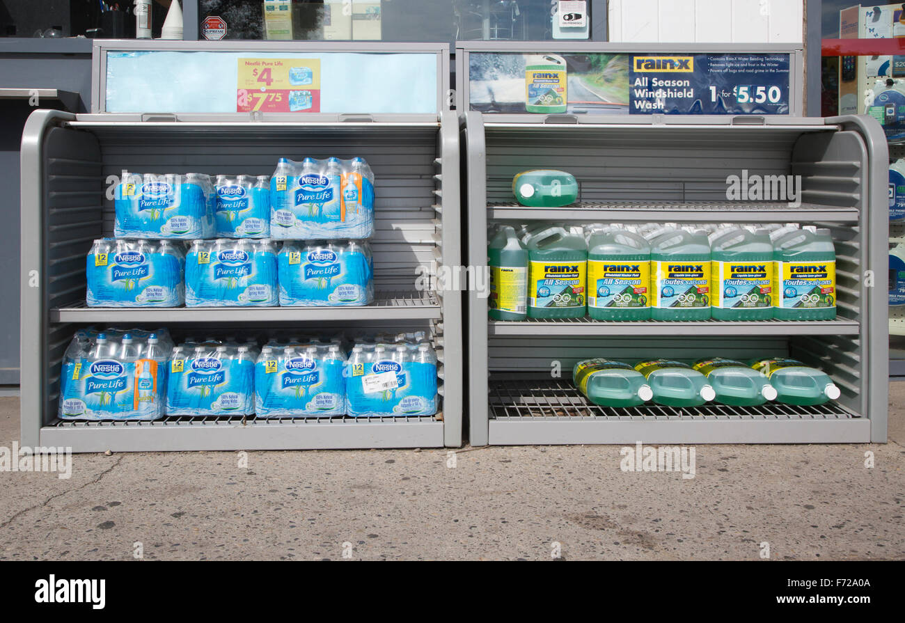 Bottled water packs wrapped in plastic and windshield washer fluid for sale at gas station. - Stock Image