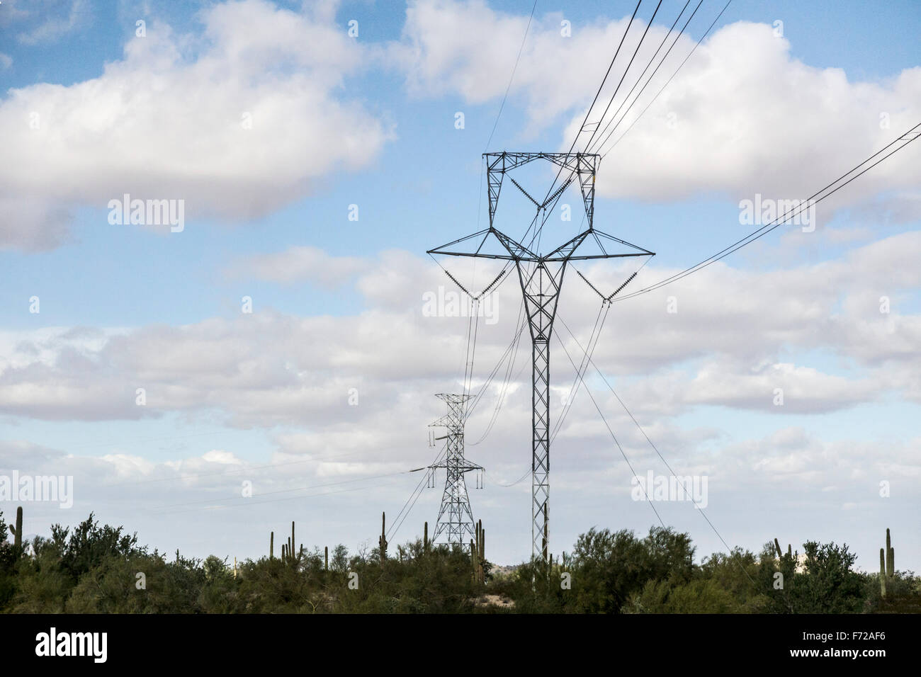 graceful filigree silhouette of towers carrying high tension voltage power lines across Sonora desert in Arizona - Stock Image