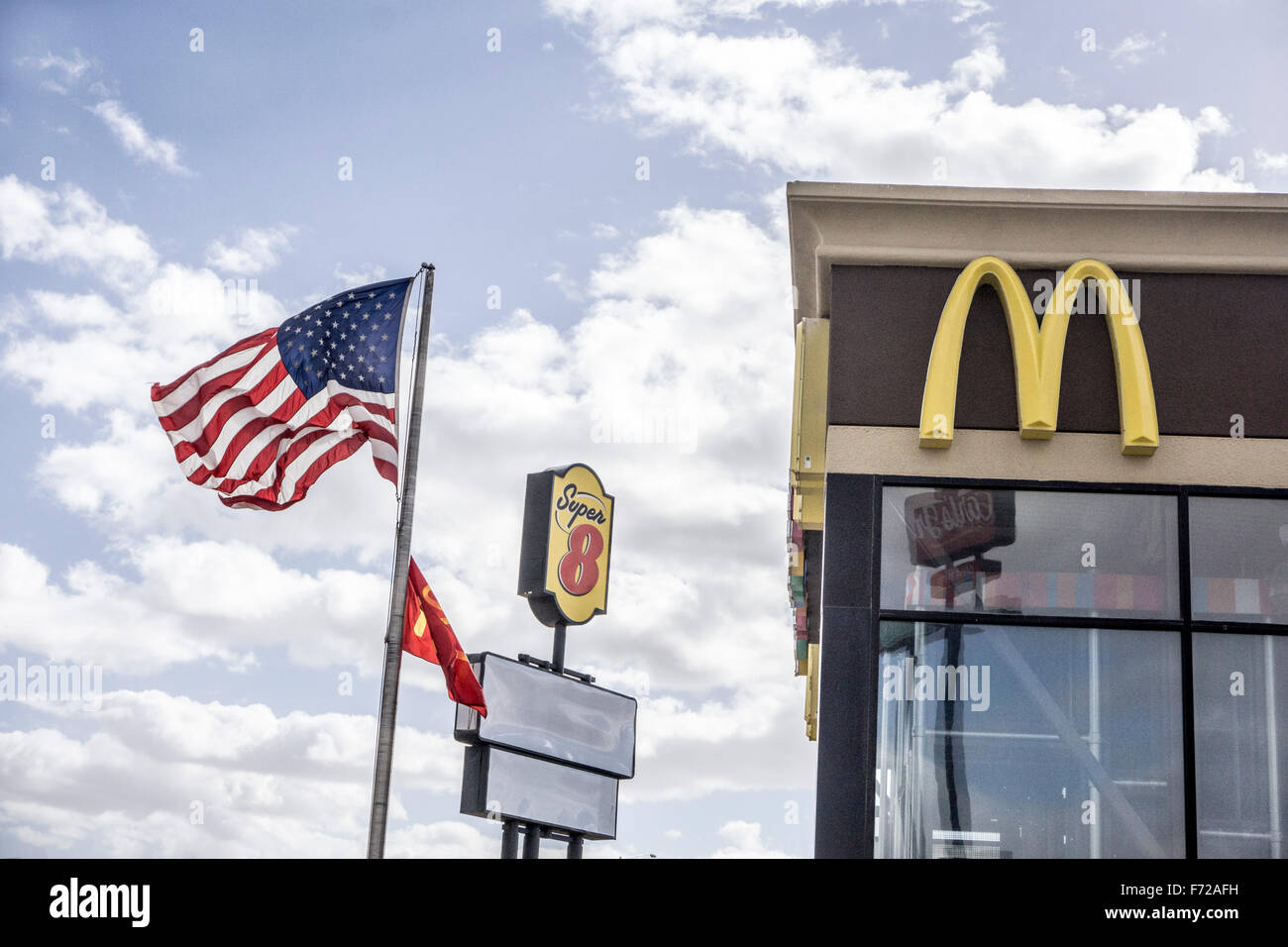 the stars & stripes fly on flagpole in brisk Arizona desert breeze next to advertising logos for 2 iconic American - Stock Image