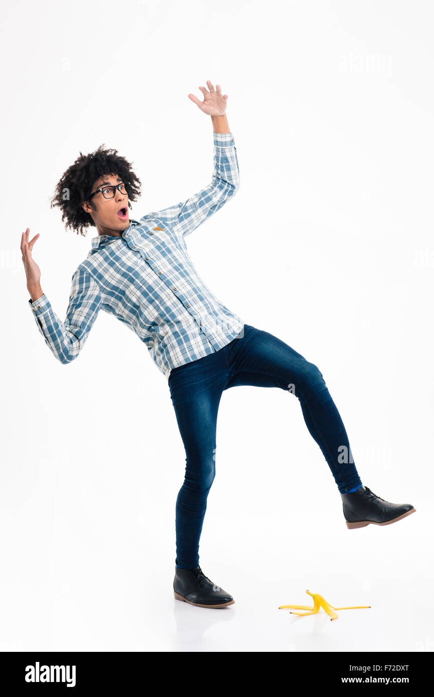 Full length portrait of a young afro american man slipping on banana skin isolated on a white background Stock Photo