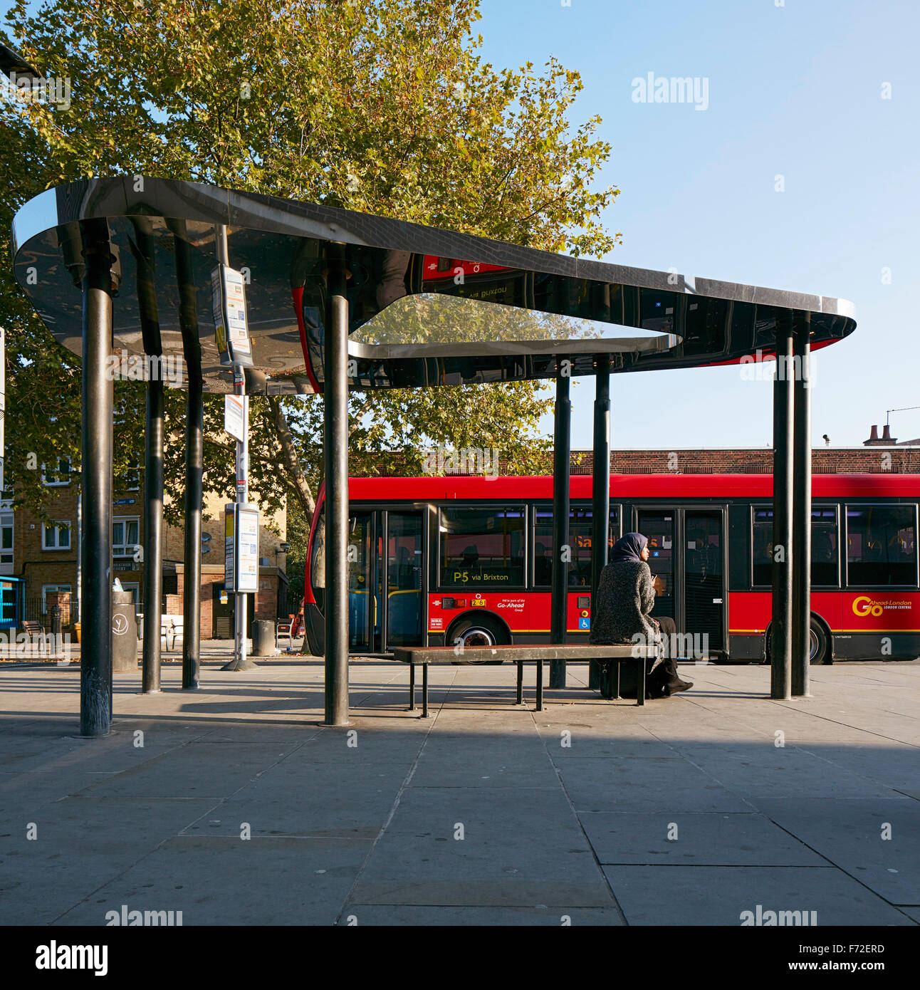 Bus shelter with London bus passing by. Binfield Road Bus Shelter, Stockwell Framework Masterplan, London, United - Stock Image
