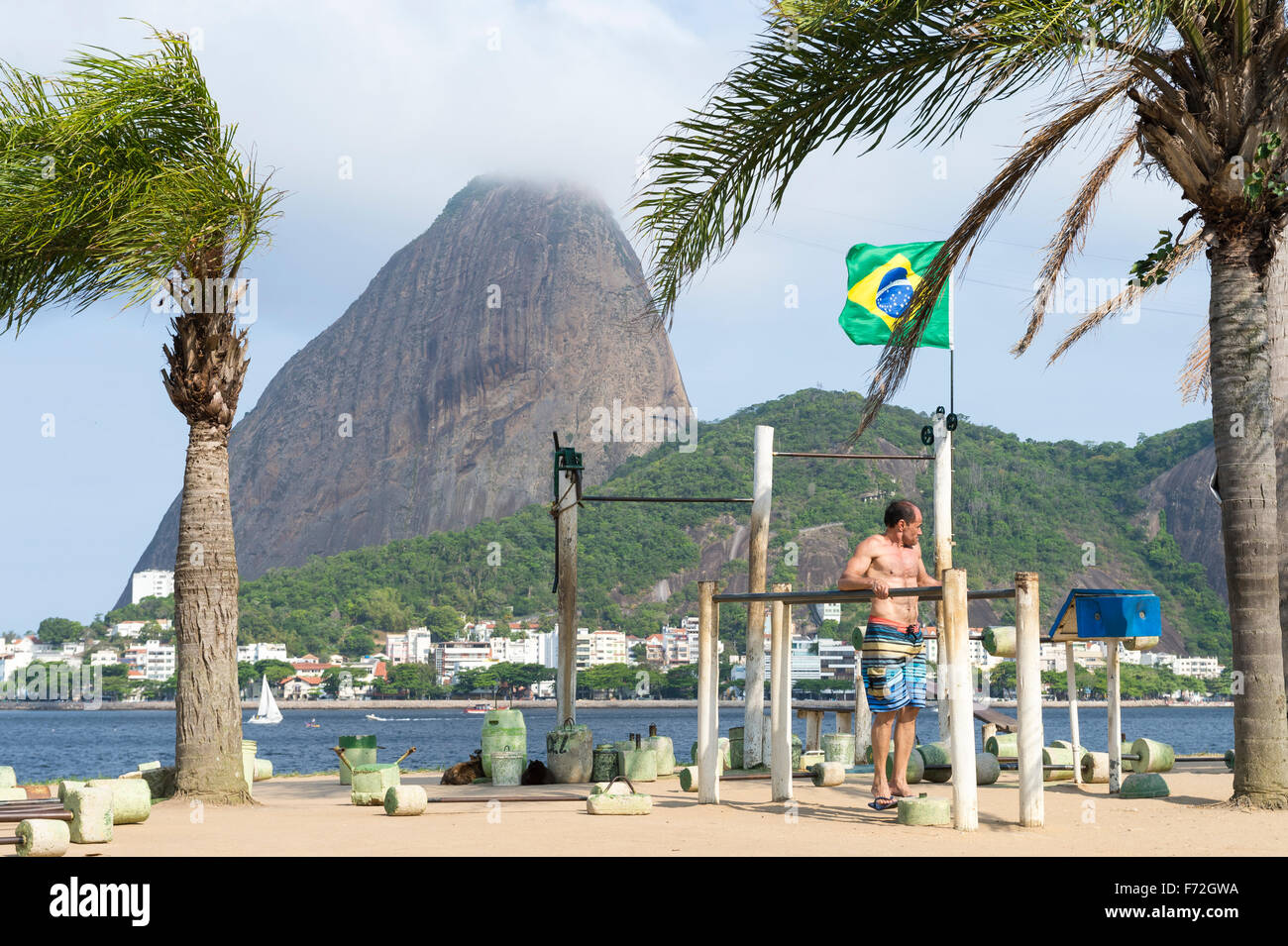 RIO DE JANEIRO, BRAZIL - OCTOBER 17, 2015: Brazilian man exercises at an outdoor workout station in the Flamengo - Stock Image