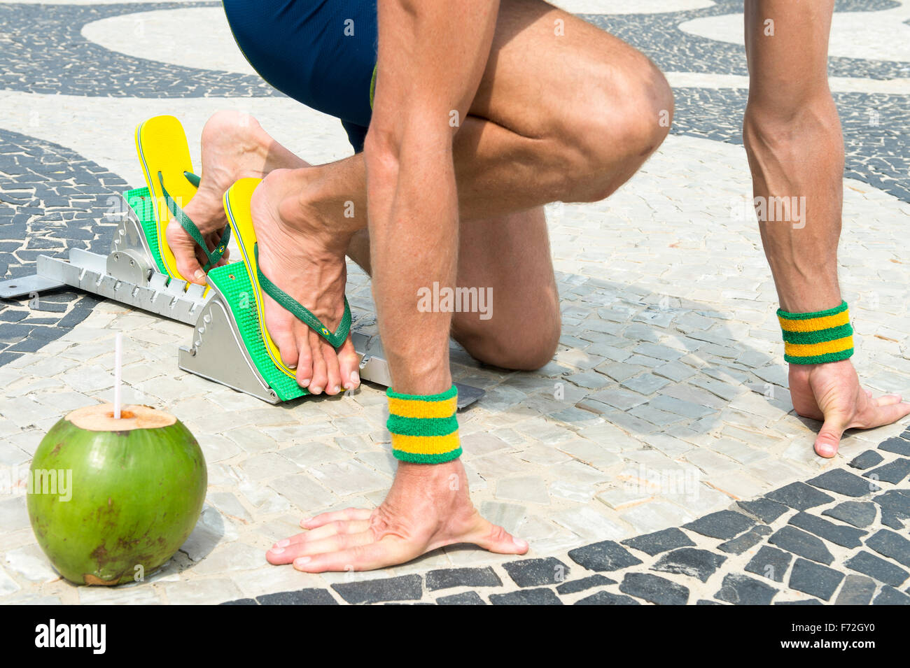 52cbde851f1faf Brazilian athlete wearing flip flops crouching at the start position in running  blocks with a coconut at Copacacabana Beach