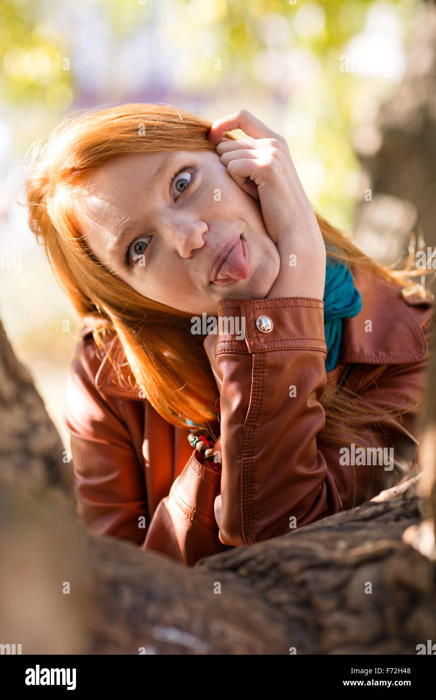 f0d1895ac Pretty amusing redhead girl making funny face and showing tongue posing in  park near tree -