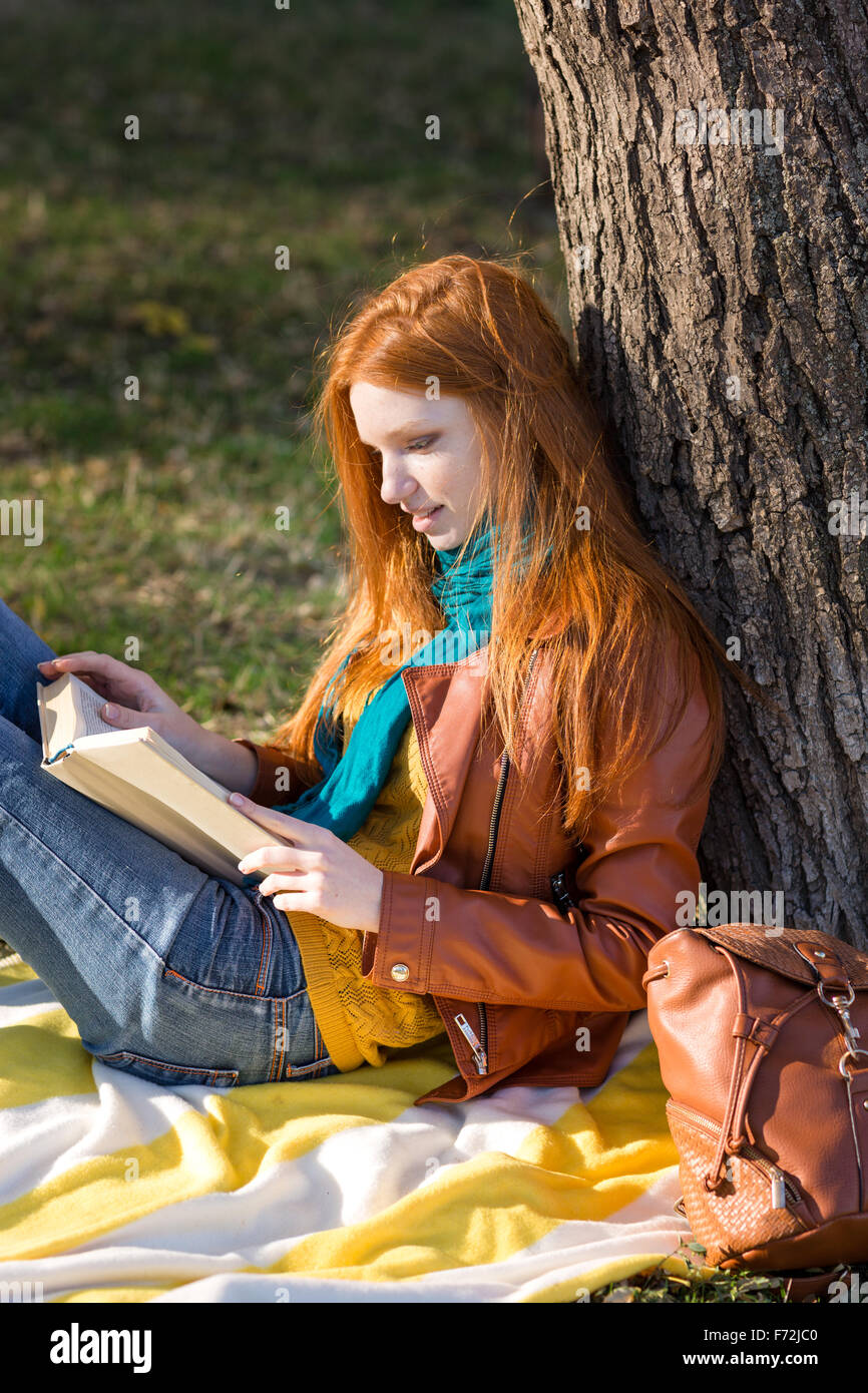 Girl reading under tree stock photos girl reading under tree stock concentrated smart girl with long red hair reading a book under the tree in park sciox Gallery