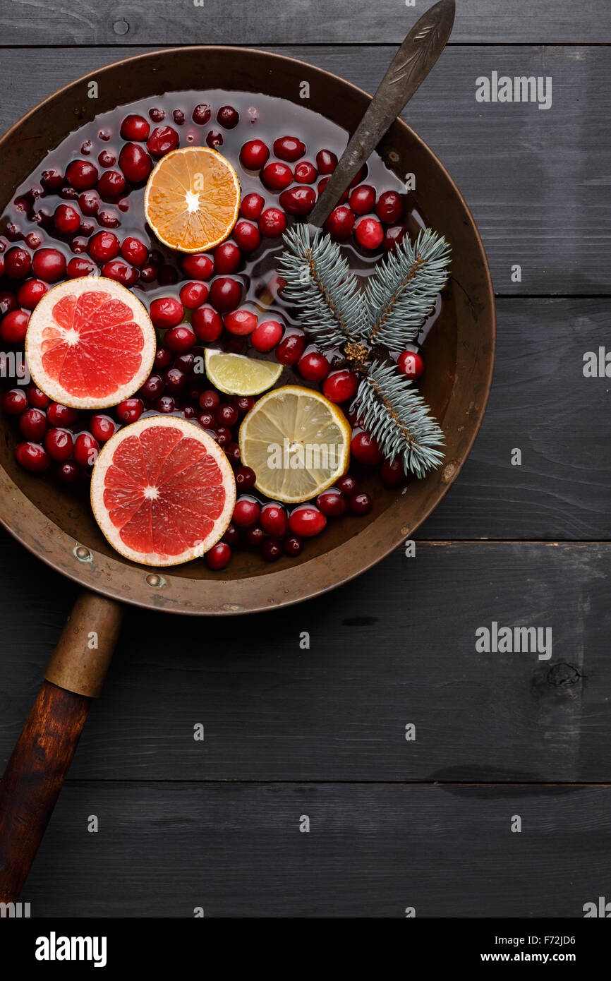 Hot winter punch,sangria,toddy or mulled wine with lemon, grapefruit,tangerine, lime and cranberry in aged rustic - Stock Image
