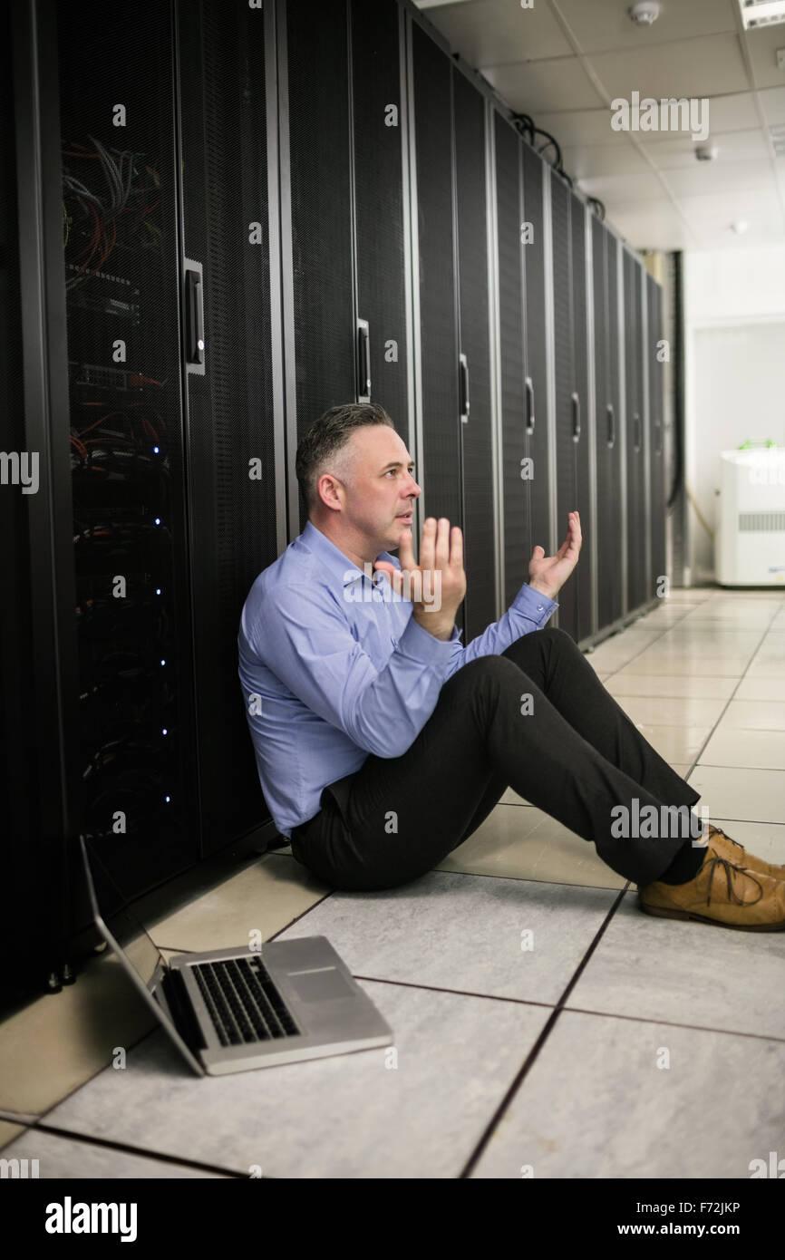 Technician feeling the pressure in server room - Stock Image