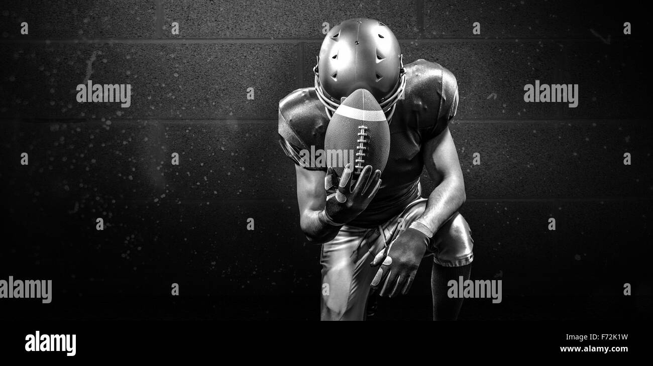 Composite image of upset american football player kneeling while holding ball - Stock Image