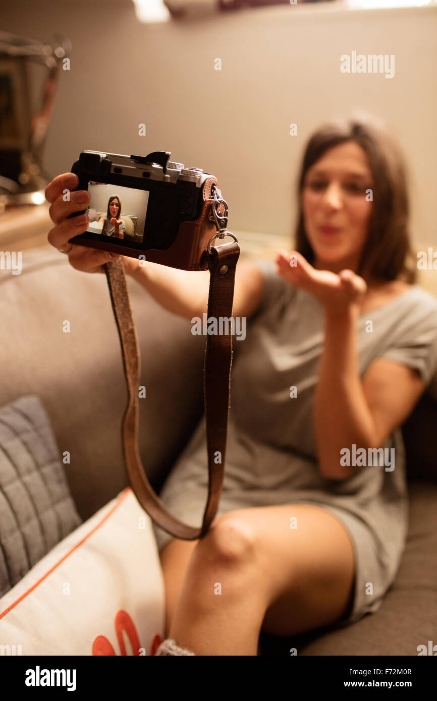 Happy woman taking selfie with camera - Stock Image