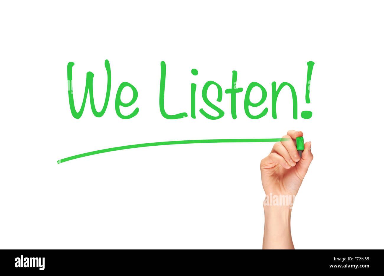We Listen, written in marker on a clear screen. - Stock Image