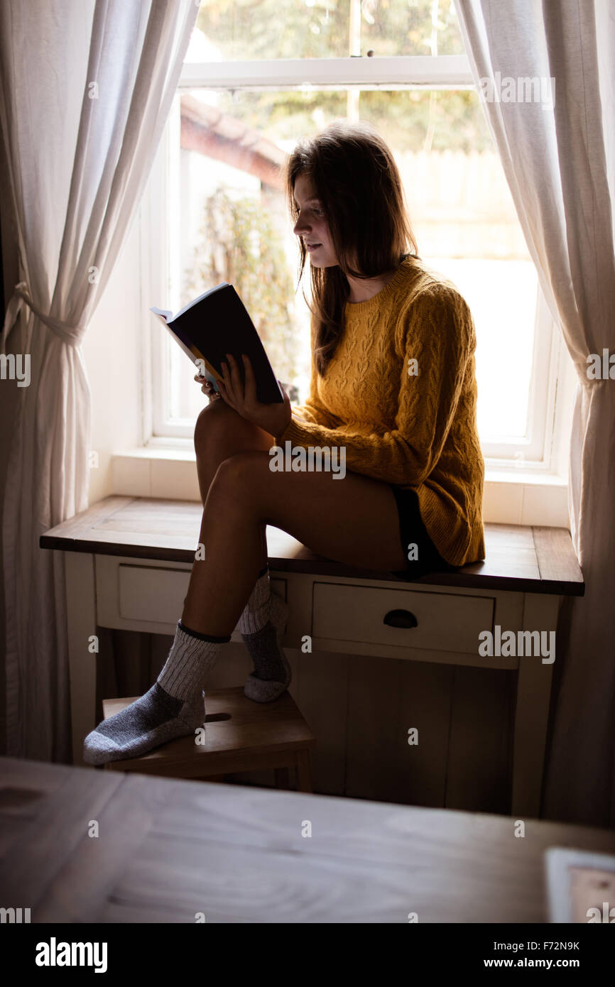 Young woman sitting on table studying Stock Photo