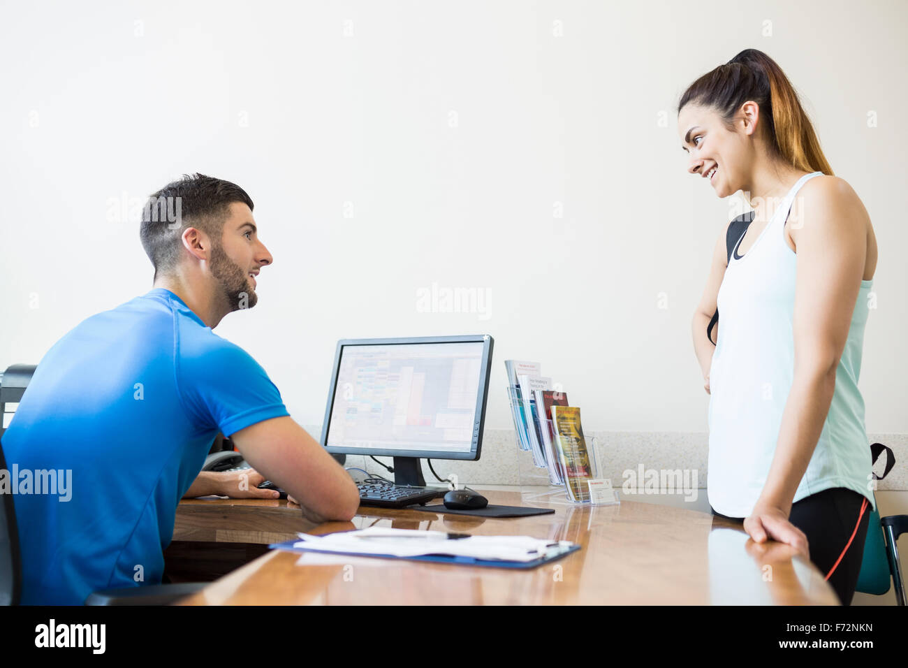 Athletic woman talking with fitness trainer Stock Photo