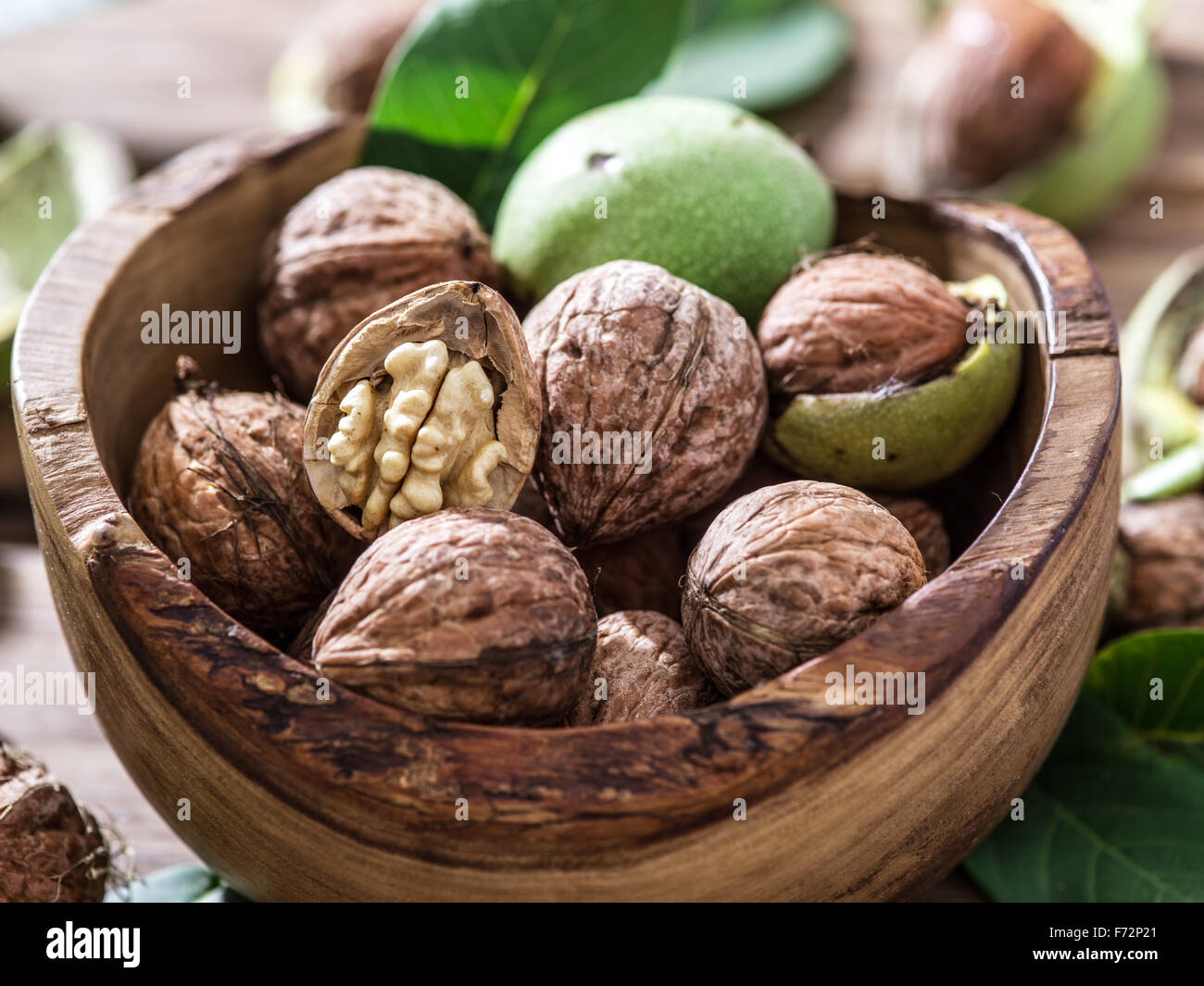 Walnuts in the wooden bowl on the table. Stock Photo