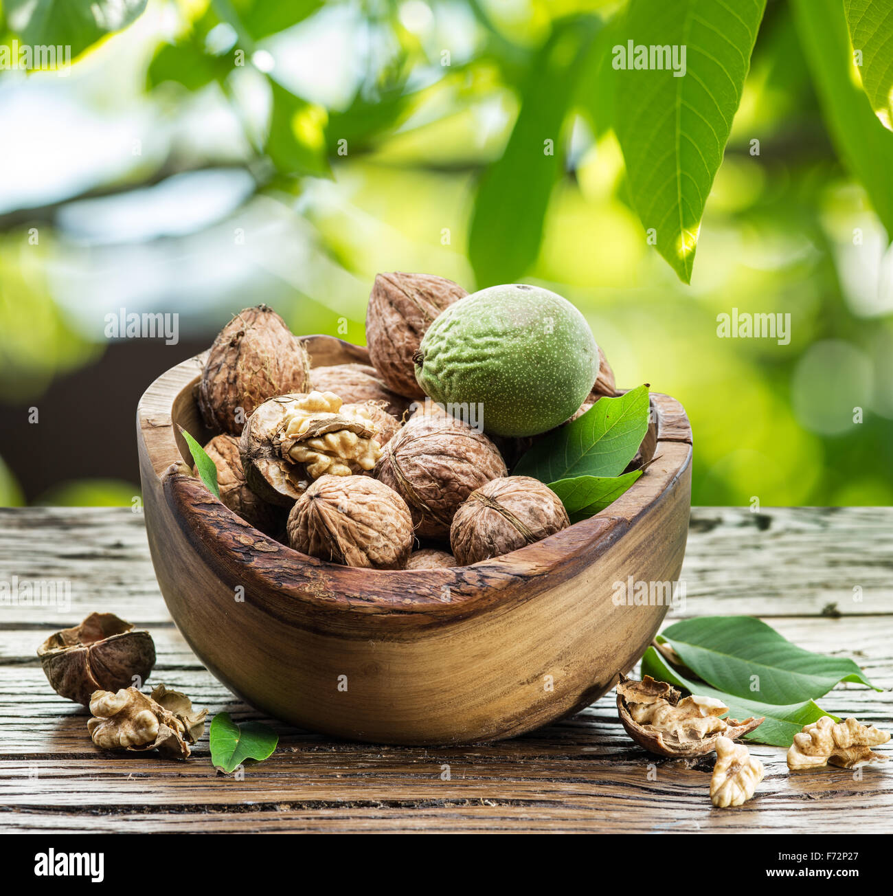 Walnuts in the wooden bowl on the table under the walnut-tree. - Stock Image